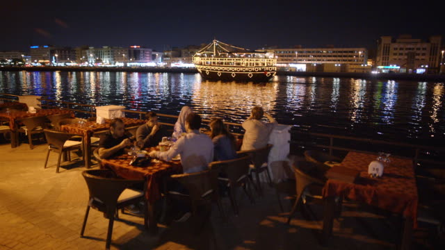 restaurant with view of passing boat - dubai creek - middle east stock videos & royalty-free footage