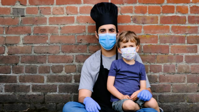 restaurant worker posing with his son, both wearing protective masks - poor family stock videos & royalty-free footage