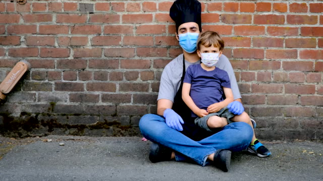 restaurant worker posing with his son, both wearing protective masks - youth unemployment stock videos & royalty-free footage