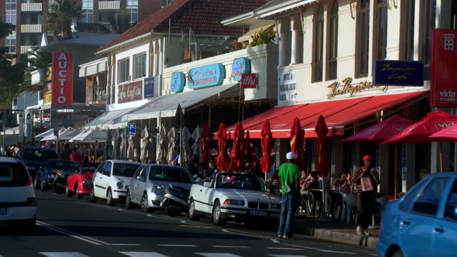 WS restaurants and shops along Camps Bay boulevard with motor cars in foreground, Cape Town, South Africa