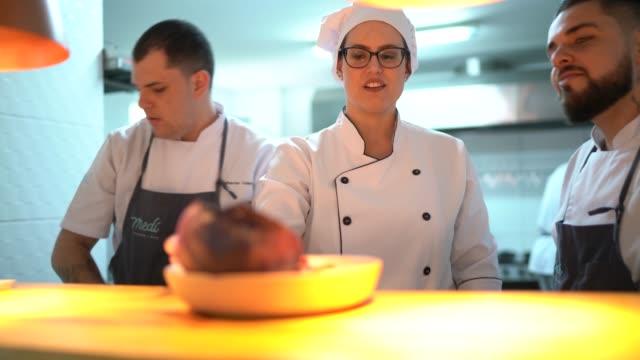 vídeos de stock, filmes e b-roll de restaurantes chef e assistente de configuração de pedidos de prato - chef de cozinha