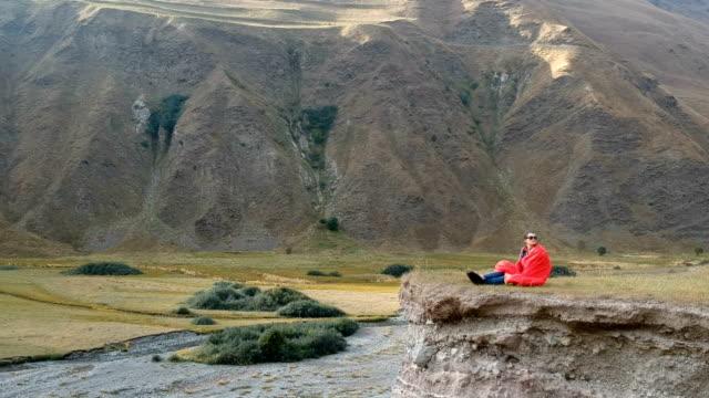 岩の上に休んでいます。山の中の女性観光客 - 寝袋点の映像素材/bロール