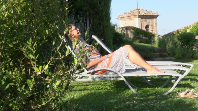 vidéos et rushes de resting sitting in a lounge chair in a small village in tuscany, italy, europe. - toscane