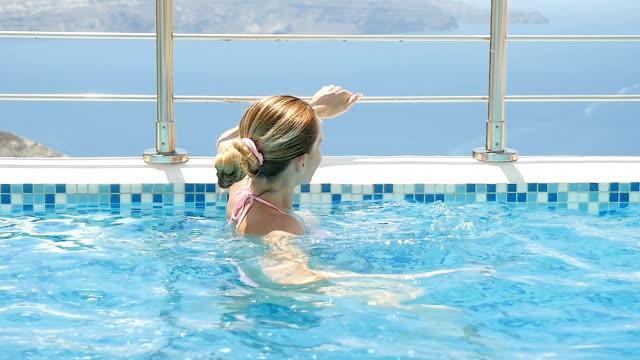 vídeos de stock, filmes e b-roll de descansando e nadar na piscina - oia santorini