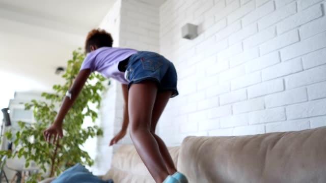 ソファの上にジャンプ、横になって落ち着きがない子 - 絆創膏点の映像素材/bロール