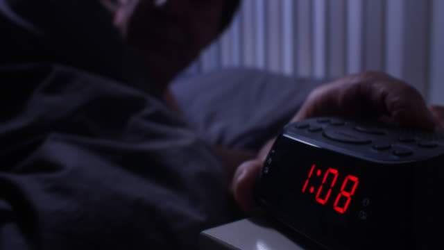 restless night can't sleep, checking the time. - ora di andare a letto video stock e b–roll