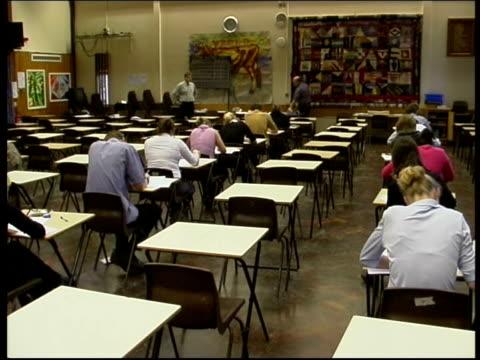 vídeos y material grabado en eventos de stock de gcse results lib seq students sitting taking exam in school hall - certificado general de educación secundaria