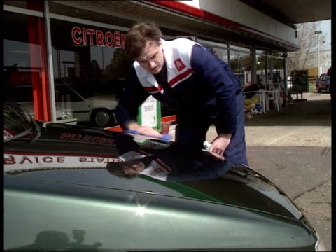 Retail car sales rise ENGLAND Cambs Duxford LS Man shining bonnet of car on forecourt of Duxford Service StationCitroen cars MS Ditto CMS Ditto MS...
