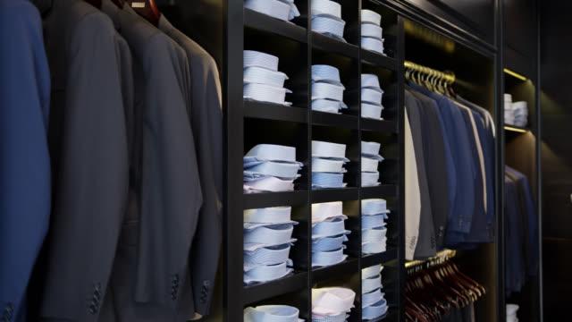 stockvideo's en b-roll-footage met de vertoning van de kleinhandels van formele mensenkleren bij een opslag - kledingrek