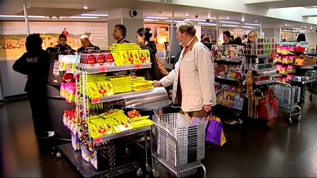vídeos y material grabado en eventos de stock de general views of marks and spencer store; shoppers, including customer with trolley, browsing shelves / customers queuing at tills / customer... - finanzas y economía