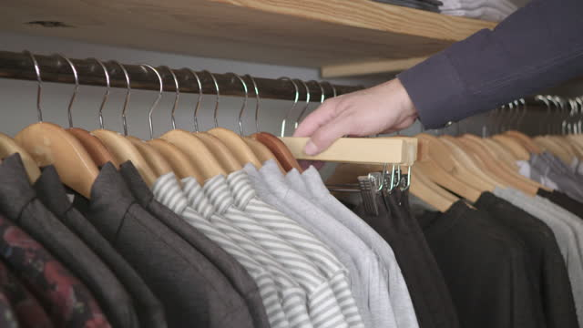 retail worker straightens rows of shirts and pants on hangars in clothing store. - wilmington north carolina stock-videos und b-roll-filmmaterial