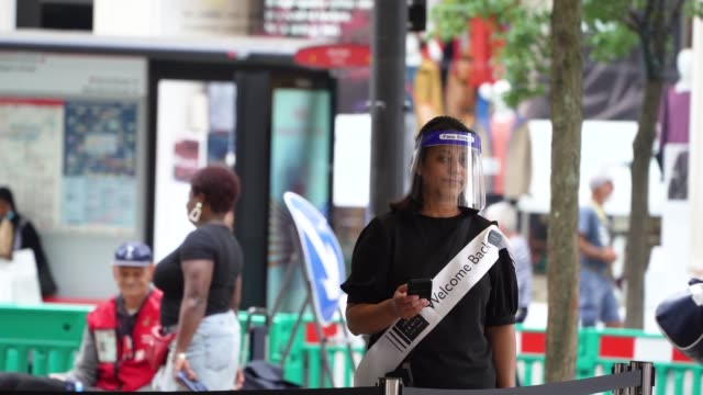 slomo a retail worker welcomes shoppers wearing a face shield on july 24 2020 in london england from today it is compulsory for shoppers to wear face... - retail stock videos & royalty-free footage