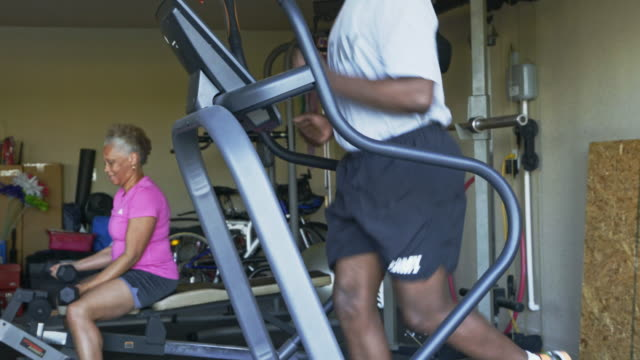 retired black couple working out in home gymnasium - treadmill stock videos & royalty-free footage