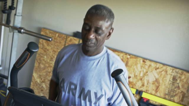 retired black man running on treadmill in home gymnasium - 自己改善点の映像素材/bロール