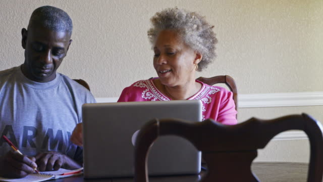 retired black military man and wife researching benefits on laptop - real wife sharing stock-videos und b-roll-filmmaterial