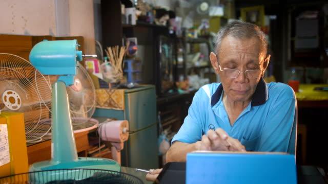 stockvideo's en b-roll-footage met gepensioneerde blanke mannen zoeken internet met behulp van digitale tablet voor fix apparatuur - tutorial