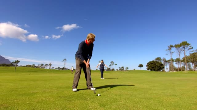 retired couple enjoying a game of golf - senior golf swing stock videos & royalty-free footage