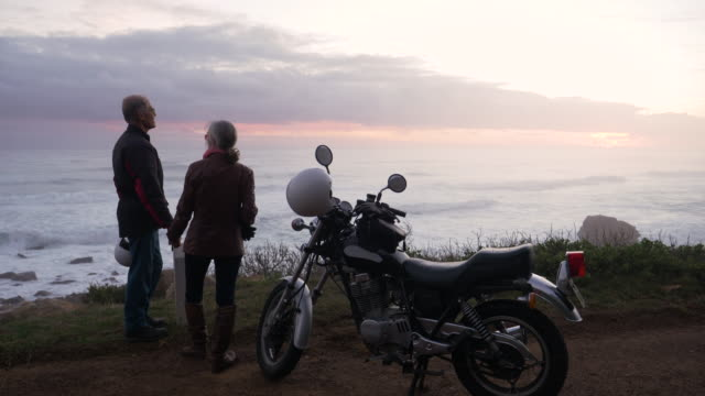 retired couple on a motorbike trip together on a coastal road. - 60 64 years stock videos & royalty-free footage