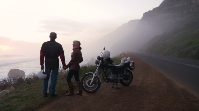 retired couple on a motorbike trip together on a coastal road. - 60 64歳点の映像素材/bロール