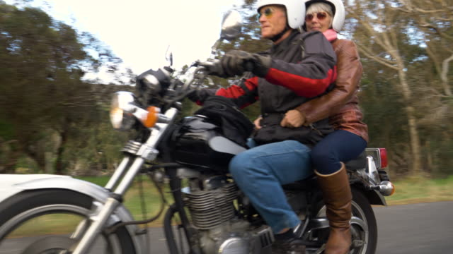 vídeos de stock e filmes b-roll de retired couple on a motorbike trip together on a country road. - casal idoso