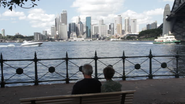 retired couple read paper as ferry passes across sydney harbour - newspaper stock videos & royalty-free footage