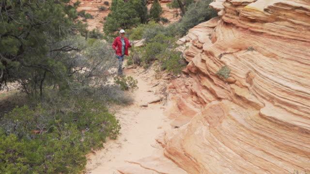 retired elderly woman walking inside red canyon in zion utah - sandstone stock videos & royalty-free footage