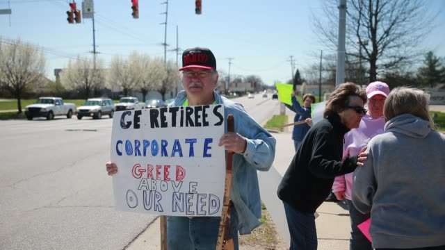 vídeos de stock e filmes b-roll de retired general electric refrigerator factory workers protest near the bloomington factory about the loss of their retiree health benefits due to... - general electric