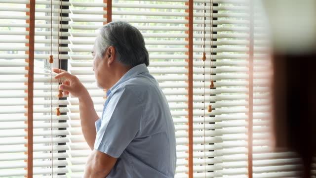vídeos de stock, filmes e b-roll de aposentado homem sozinho em casa. triste velho sozinho perto de uma janela e a pensar numa coisa: tristeza e depressão em uma filmagem iluminação natural - condição médica