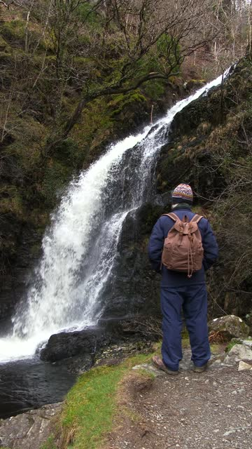 retired man looking at a waterfall on a spring day - johnfscott stock videos & royalty-free footage