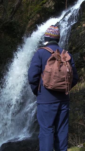 retired man standing close to a waterfall - johnfscott stock videos & royalty-free footage
