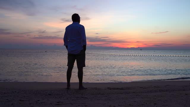 vídeos de stock, filmes e b-roll de um velho aposentado de pé com os braços abertos para o ar da manhã na praia. implica esperança, solidão ou a alegria de viver sozinho. - beach holiday
