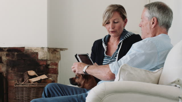Retired Senior Couple at home with digital tablet