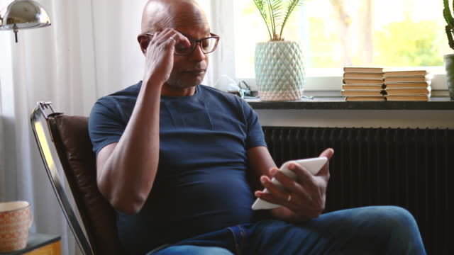 retired senior man adjusting eyeglasses while reading e-book in room at home - electronic book stock videos & royalty-free footage