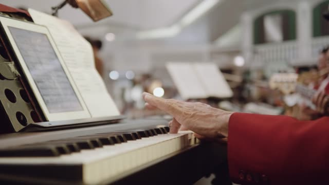 Retired senior man playing piano on stage.
