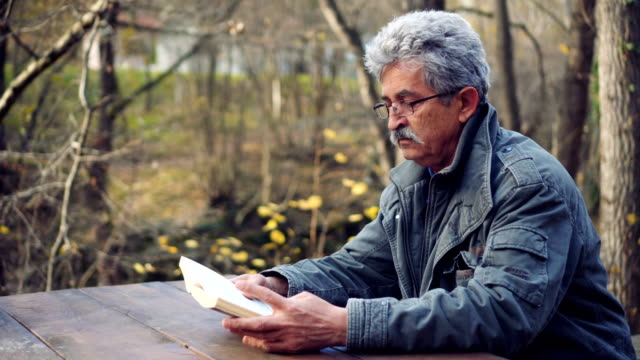 Retired senior man read book in nature