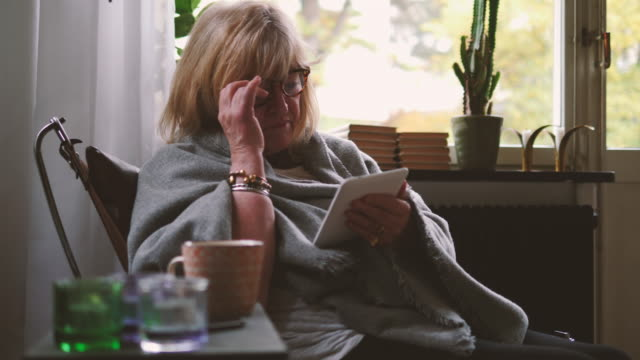 Retired senior woman adjusting eyeglasses while reading e-book at home