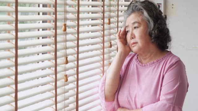 retired woman alone in home.sad old woman standing alone near a window and thinking about something: sadness and depression in a natural lighting footage - memorial stock videos & royalty-free footage