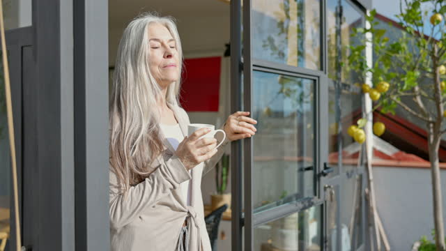 vidéos et rushes de femme retraité prenant une pause pour le soleil et le café sur le pont - yeux fermés