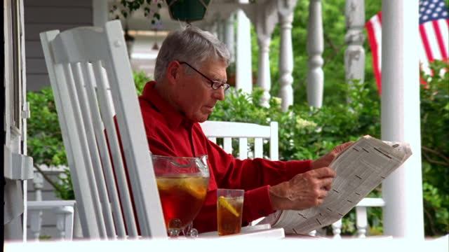a retiree reads the newspaper on his front porch. - one senior man only stock-videos und b-roll-filmmaterial