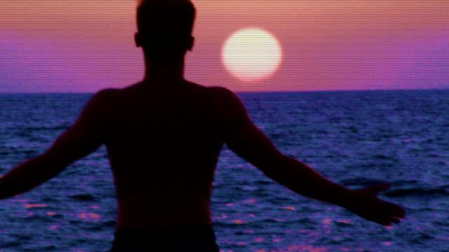 retro man meditation. rocky coastline - person cross legged stock videos & royalty-free footage