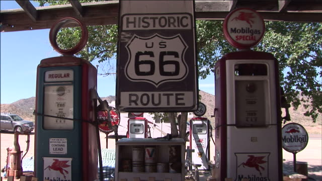 vidéos et rushes de a retro route 66 gas station features gas pumps and displays from the past. - route 66