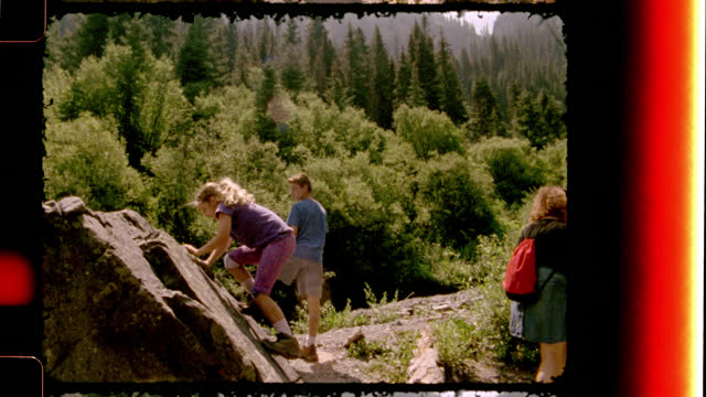 retro style film footage of a mom and two kids on scenic hiking trail and girl climbing rocks on family camping trip to colorado. - filmrolle stock-videos und b-roll-filmmaterial