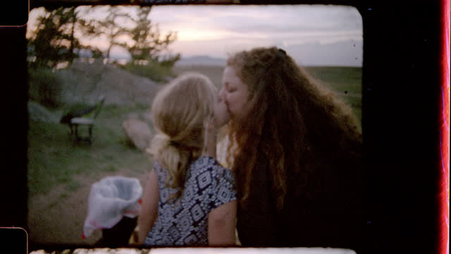 retro style film footage of mother and daughter sharing a sweet kiss at picnic table and daughter turning to kiss camera on family camping trip. - di archivio video stock e b–roll