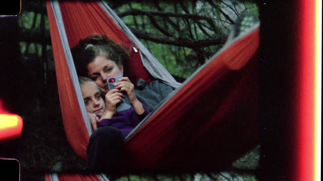 retro style film footage of mother and daughter with smartphone sharing a cozy hammock on family camping trip to rio grande del norte national monument. - wonderlust stock videos & royalty-free footage