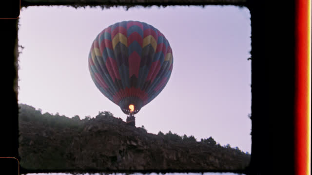 Retro style film footage of young girl in natural hot spring gazing up at hot air balloon on New Mexico camping trip.