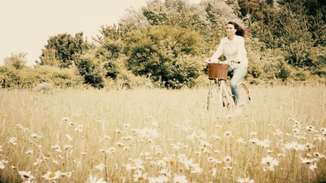 retro style, young woman cycling through a meadow, riding a retro bicycle. - grass family stock videos & royalty-free footage