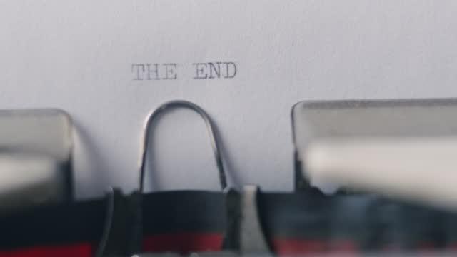 vídeos y material grabado en eventos de stock de máquina de escribir vintage retro escribe texto en el viejo libro blanco - the end