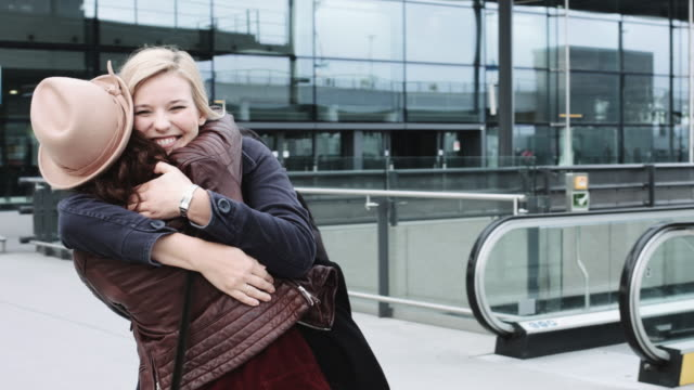 reunited and hugging friends on airport arrival - ankomst bildbanksvideor och videomaterial från bakom kulisserna