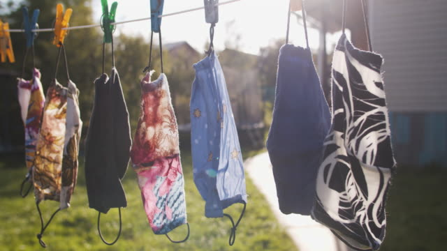 reusable fabric protective face masks hanging outdoors and drying in a sunny day - hanging stock videos & royalty-free footage