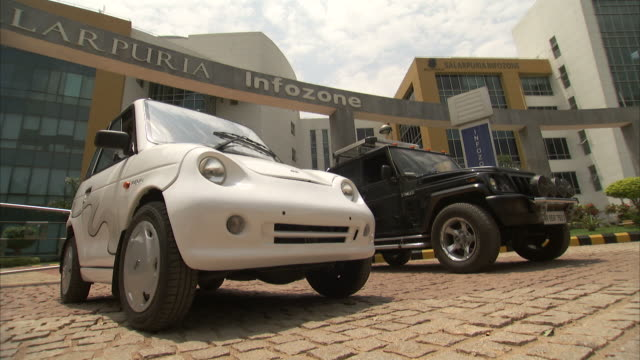 A Reva electric car pulls away from a car lot.
